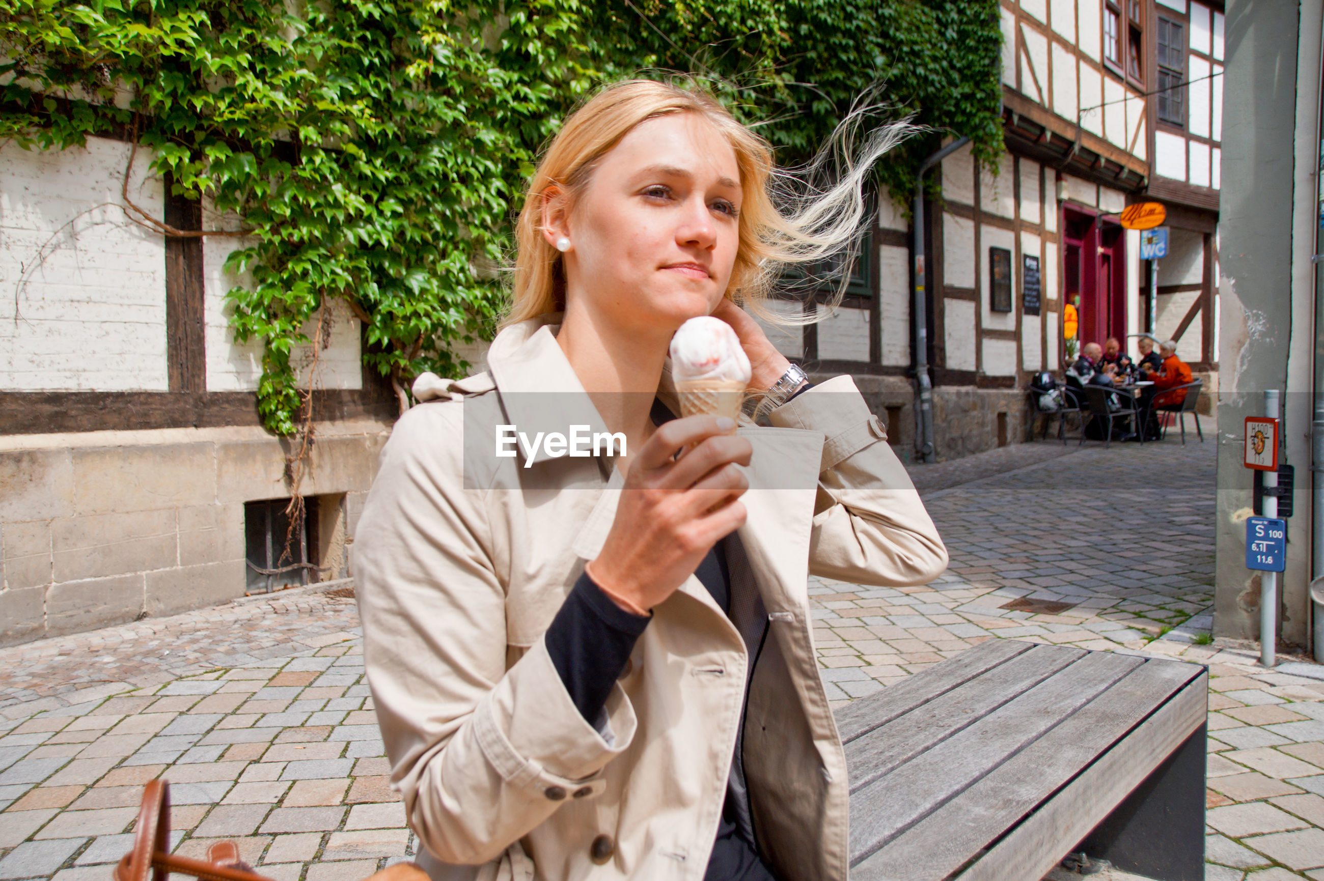 Young woman eating ice cream while sitting on bench in city