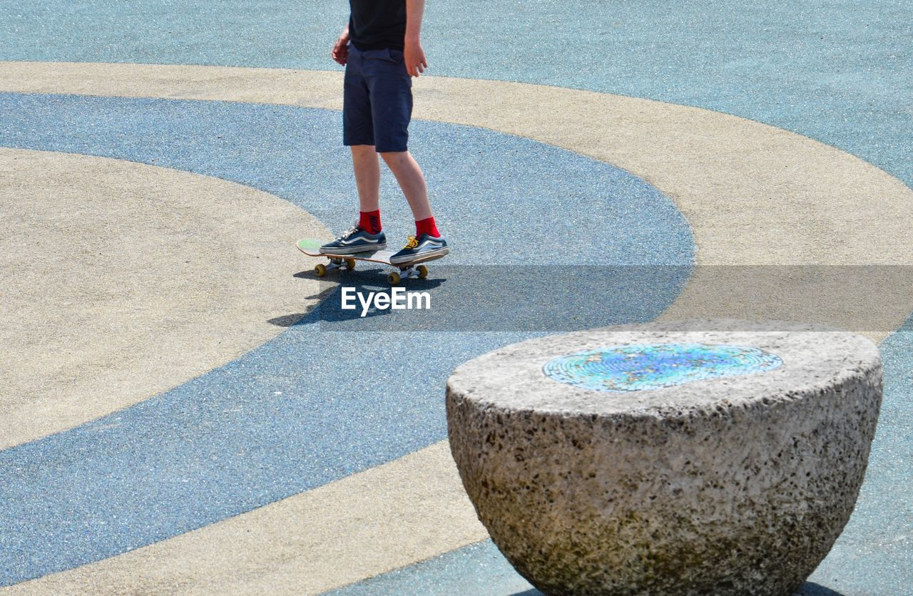 Low Section Of Boy Standing On Skateboard At Playground During Sunny Day