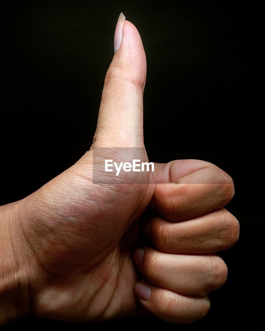 CLOSE-UP OF PERSON HAND OVER BLACK BACKGROUND