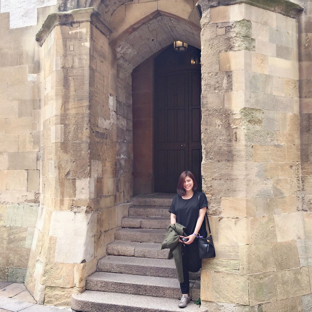 Portrait Of Smiling Young Woman Standing On Steps Against Windsor Castle