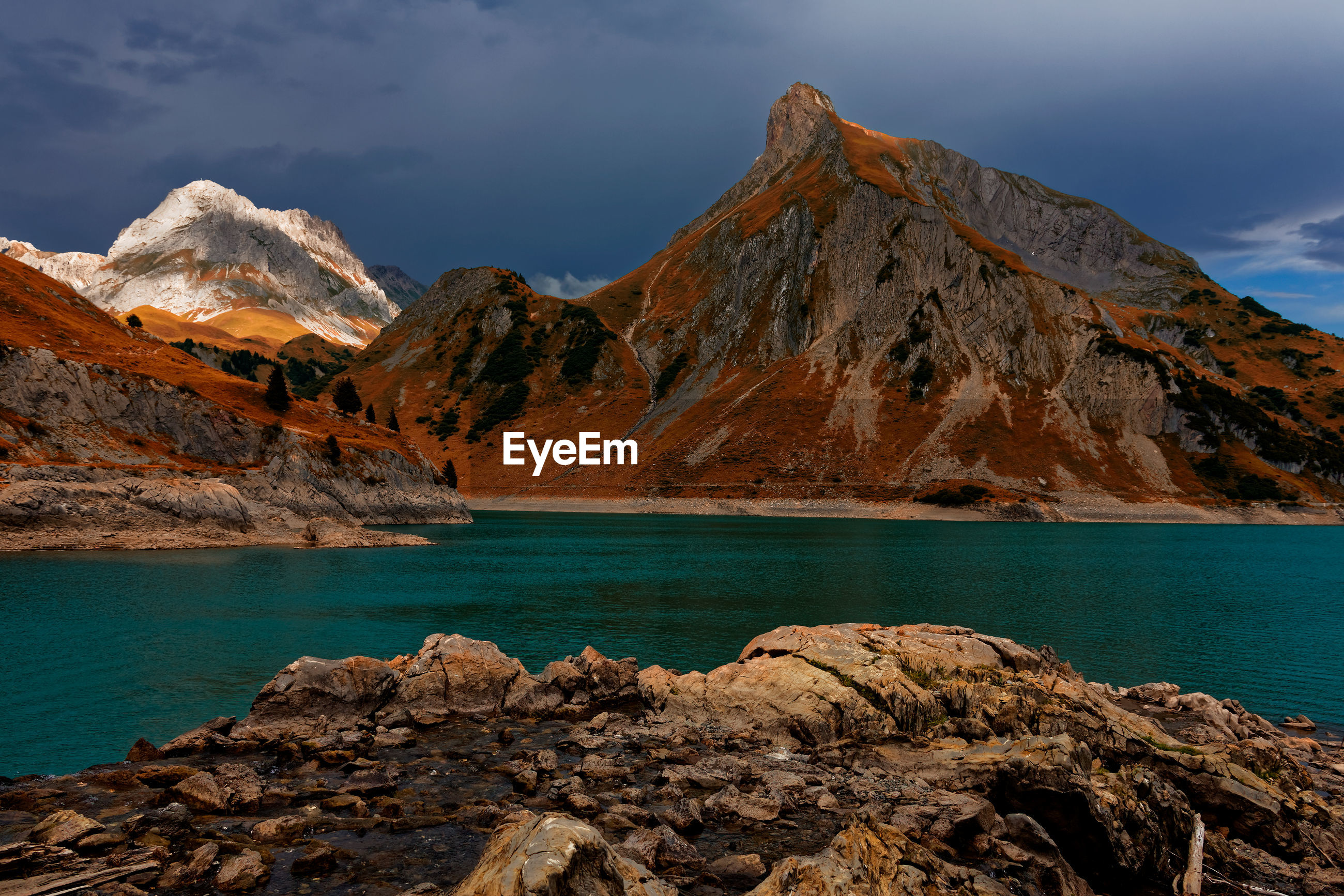 SCENIC VIEW OF ROCKS BY LAKE AGAINST SKY