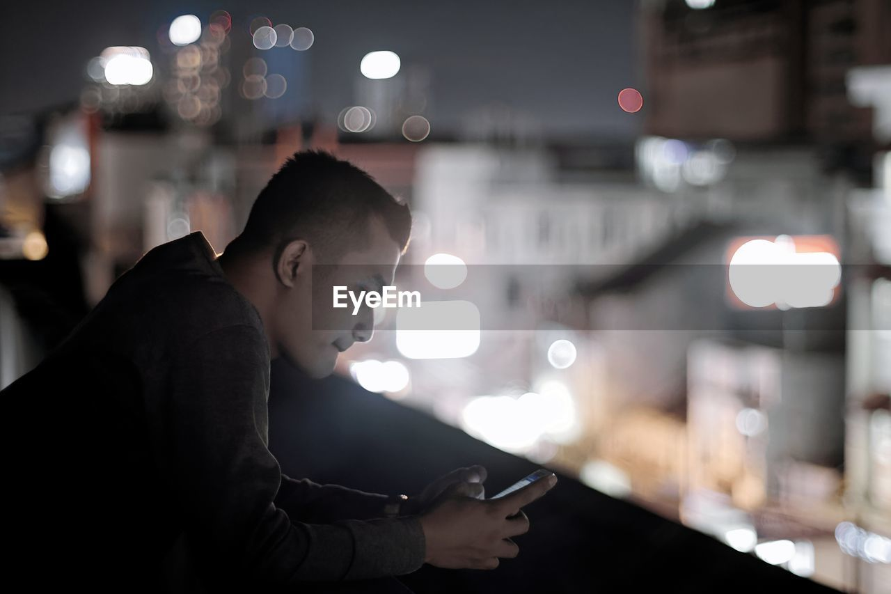 Side View Of Young Man Using Smart Phone At Night