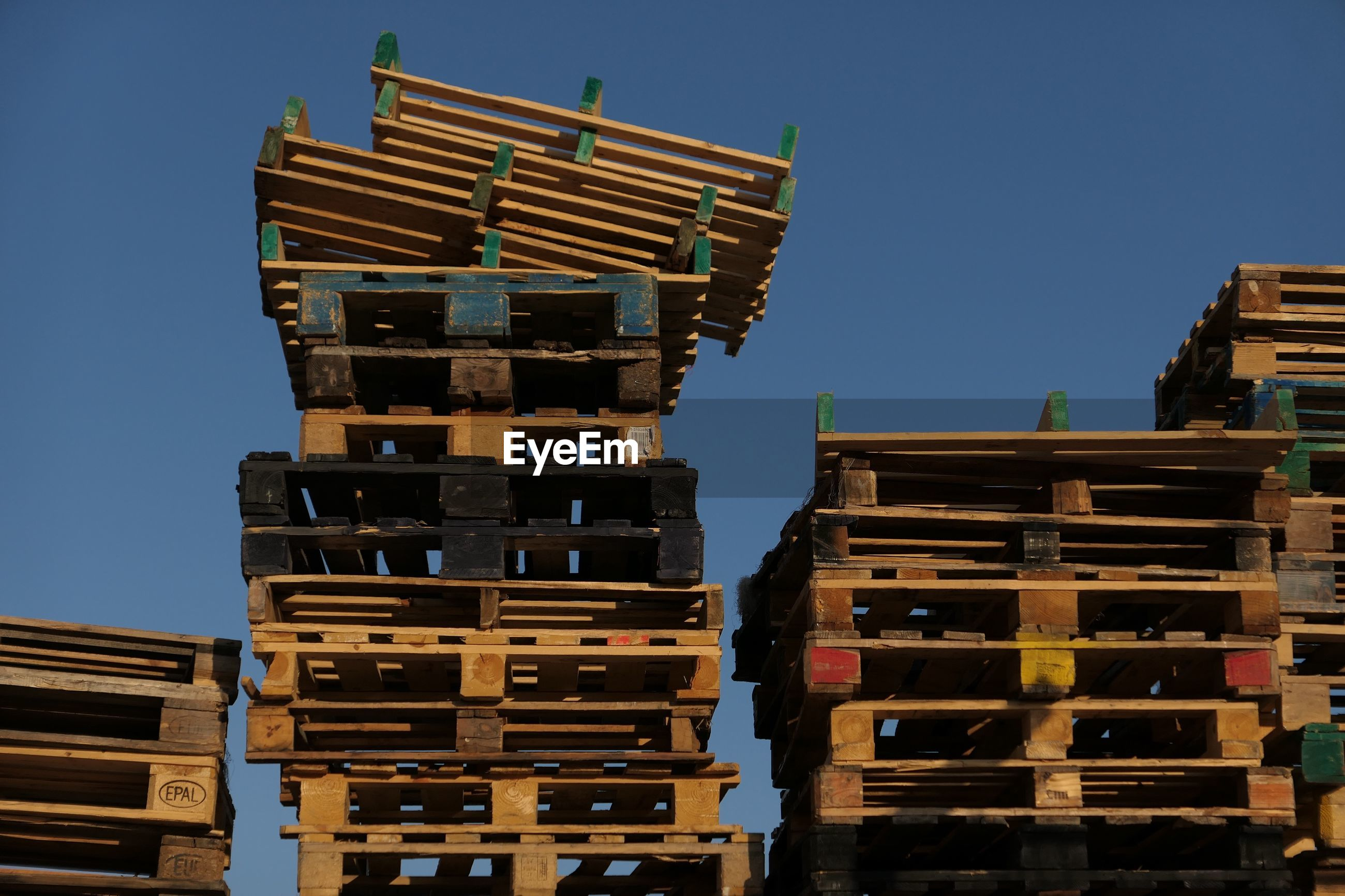 Low angle view of stacked wooden pallets against clear blue sky