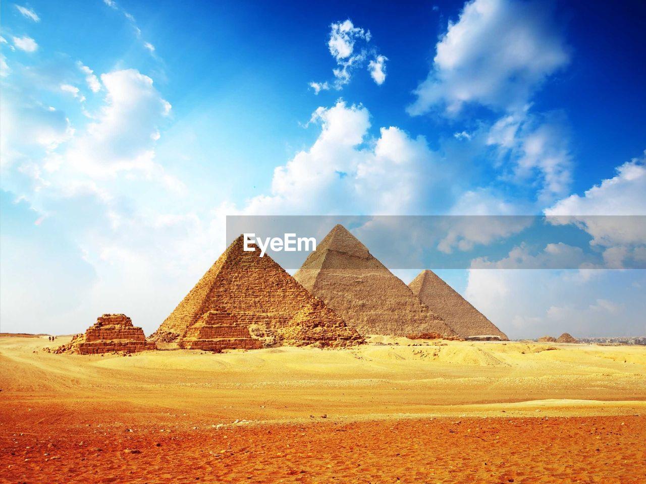 Pyramids in desert against cloudy sky