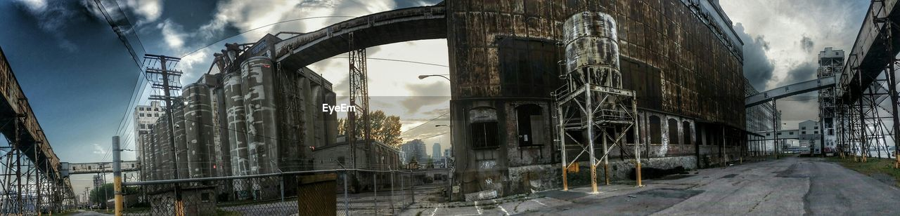 Panoramic View Of Abandoned Factory Against Cloudy Sky