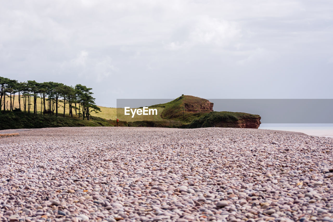sky, beauty in nature, tranquility, tranquil scene, scenics - nature, nature, land, cloud - sky, rock, day, solid, plant, no people, sea, water, pebble, beach, surface level, stone, outdoors, gravel