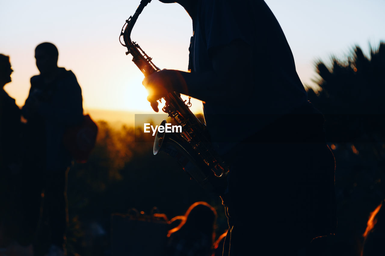 sky, sunset, playing, men, real people, musical instrument, silhouette, orange color, guitar, music, leisure activity, nature, string instrument, lifestyles, arts culture and entertainment, people, musical equipment, musician, outdoors