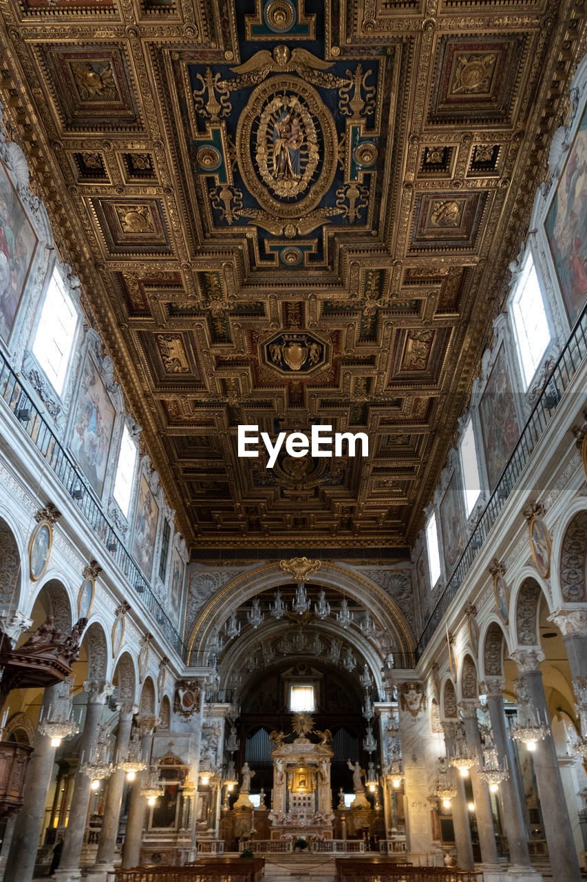 ceiling, architecture, indoors, built structure, low angle view, travel destinations, illuminated, religion, place of worship, lighting equipment, arch, no people, belief, ornate, travel, spirituality, building, architectural feature, tourism, architectural column, mural, architecture and art, luxury