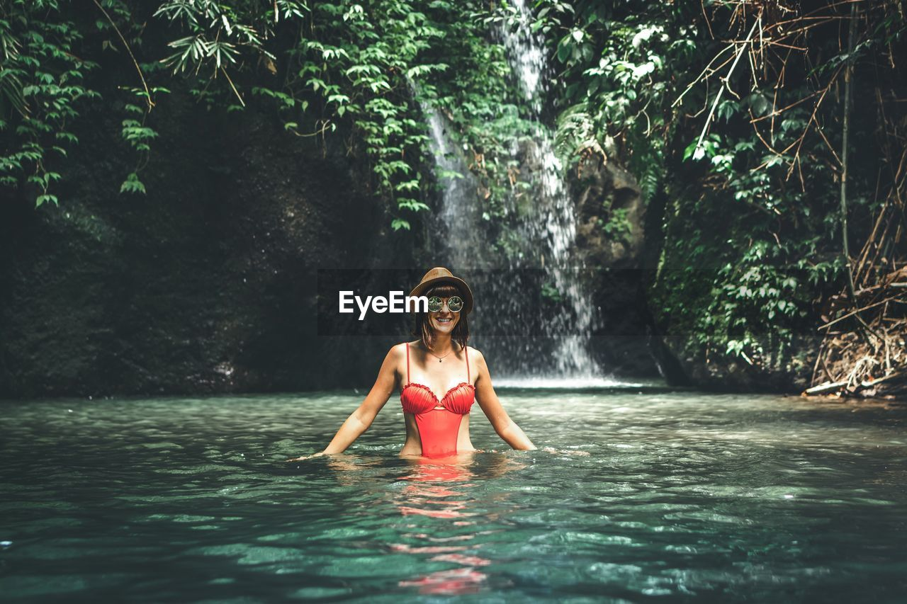 water, tree, one person, waterfront, leisure activity, lifestyles, front view, young adult, real people, young women, forest, nature, plant, day, portrait, looking at camera, women, swimwear, beauty in nature, outdoors, fashion, beautiful woman