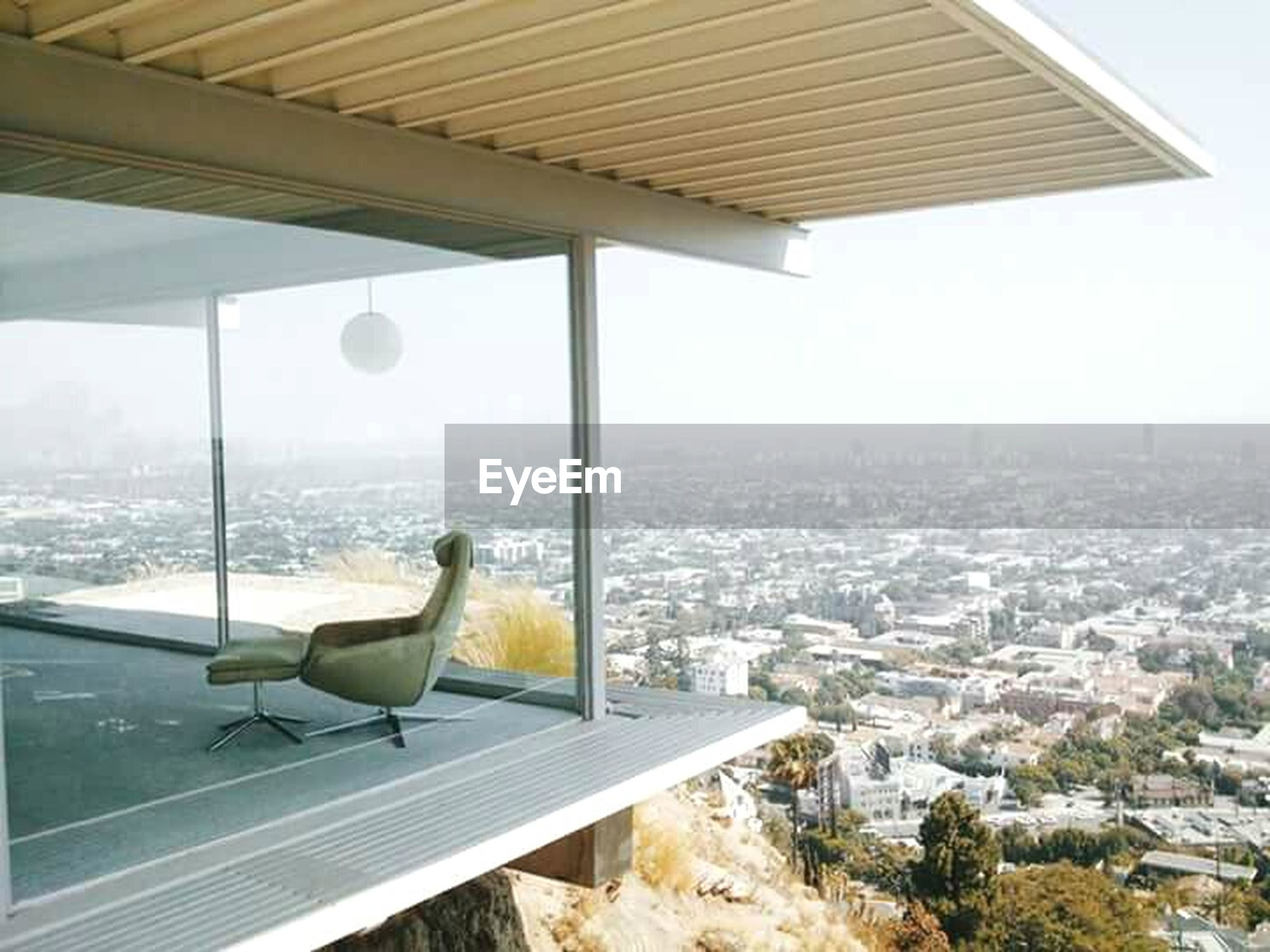cityscape, architecture, built structure, city, building exterior, window, indoors, sky, glass - material, one person, transparent, flying, day, clear sky, looking through window, sunlight, modern, sea, high angle view, skyscraper