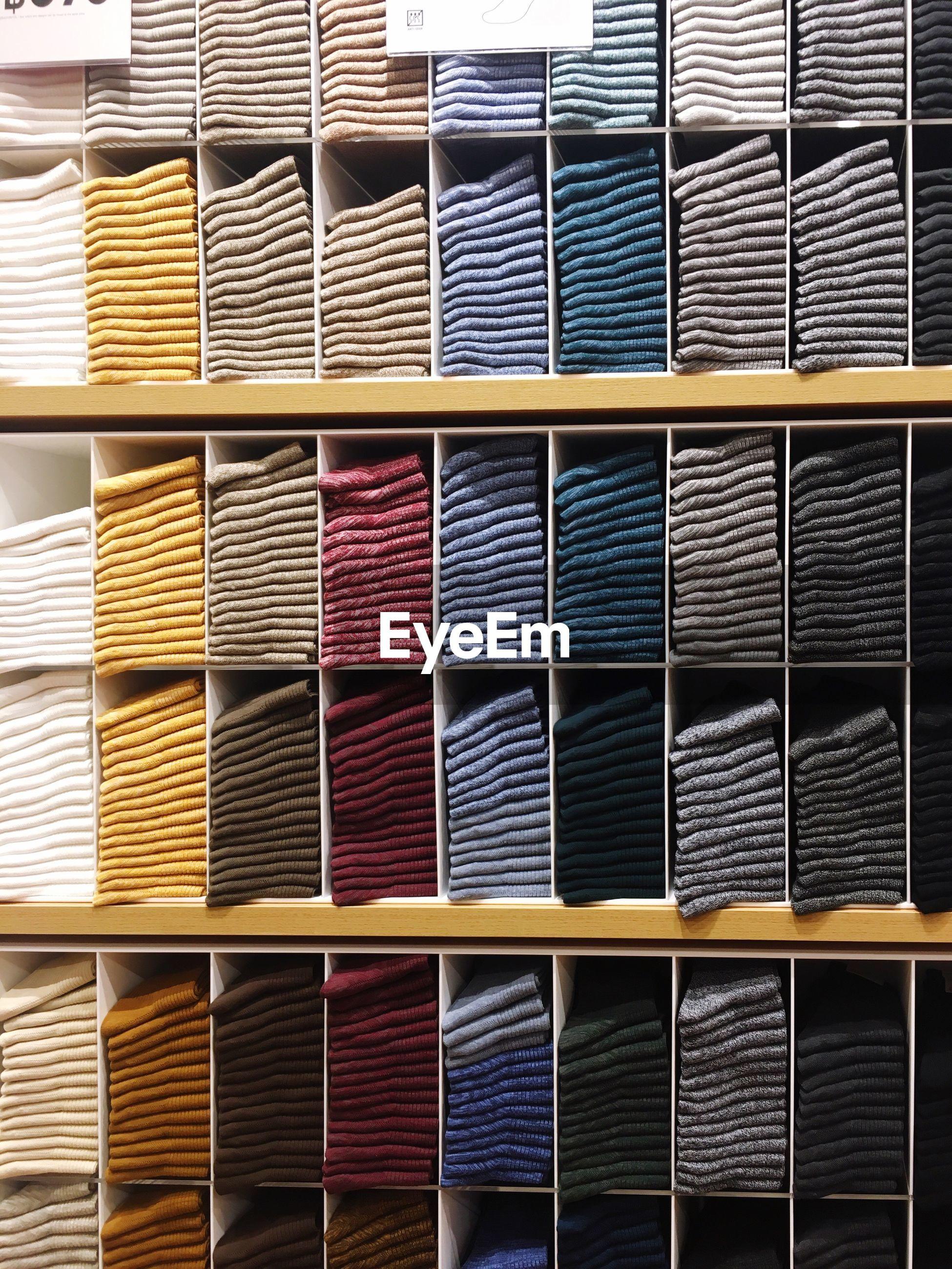 Full frame shot of clothing on shelves for sale at store