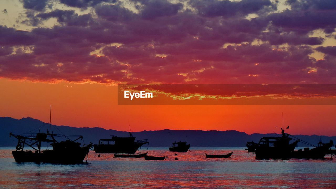SILHOUETTE OF BOATS MOORED IN SEA AGAINST CLOUDY SKY
