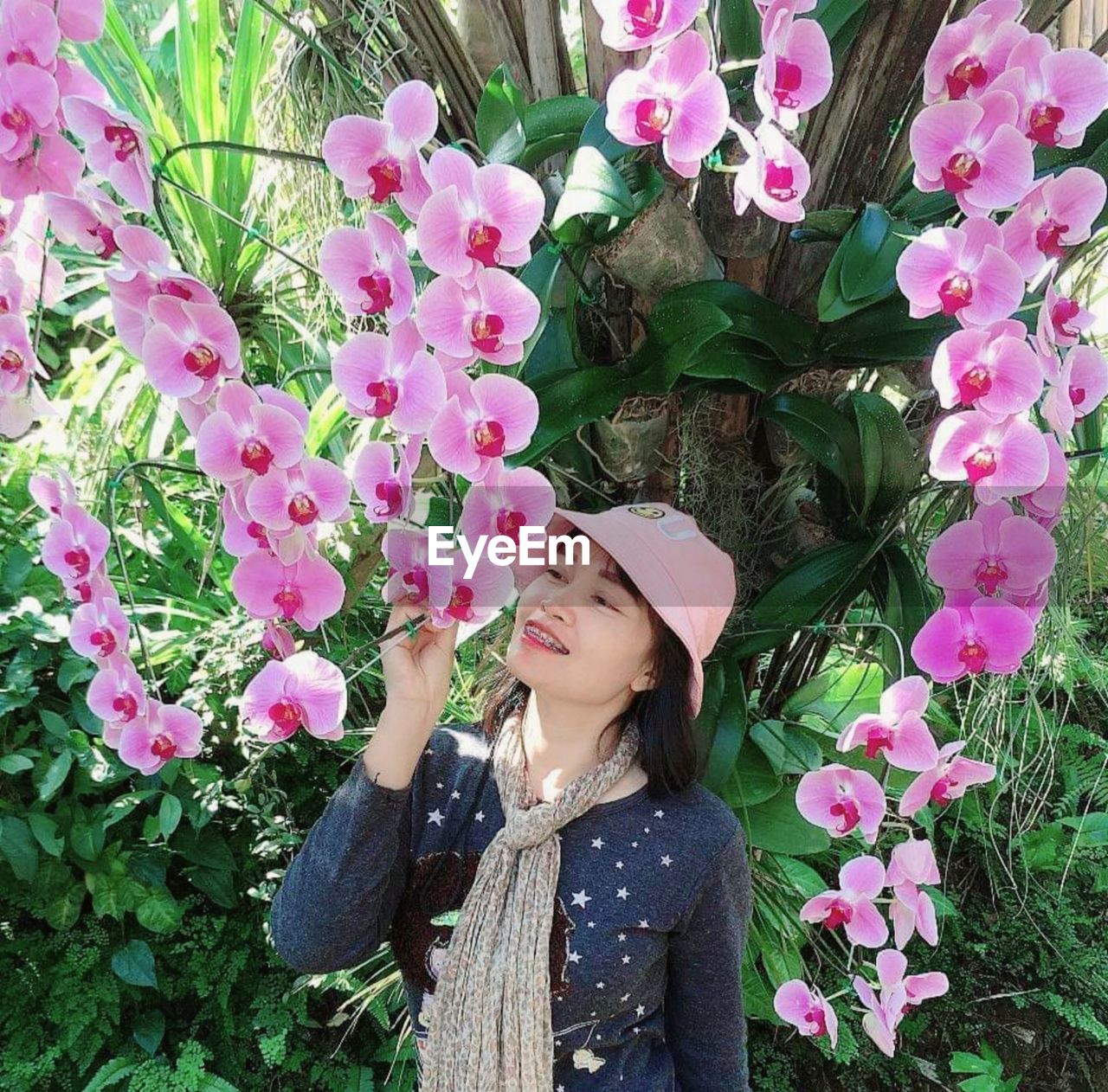 BEAUTIFUL YOUNG WOMAN STANDING BY PINK FLOWERS