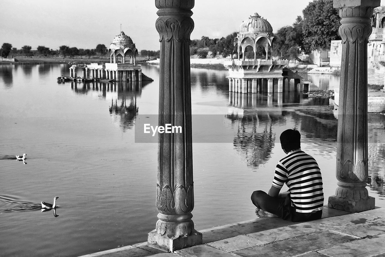 rear view, water, sitting, real people, one person, architecture, built structure, men, building exterior, spirituality, lifestyles, day, leisure activity, nature, religion, belief, casual clothing, place of worship, architectural column, outdoors, looking at view