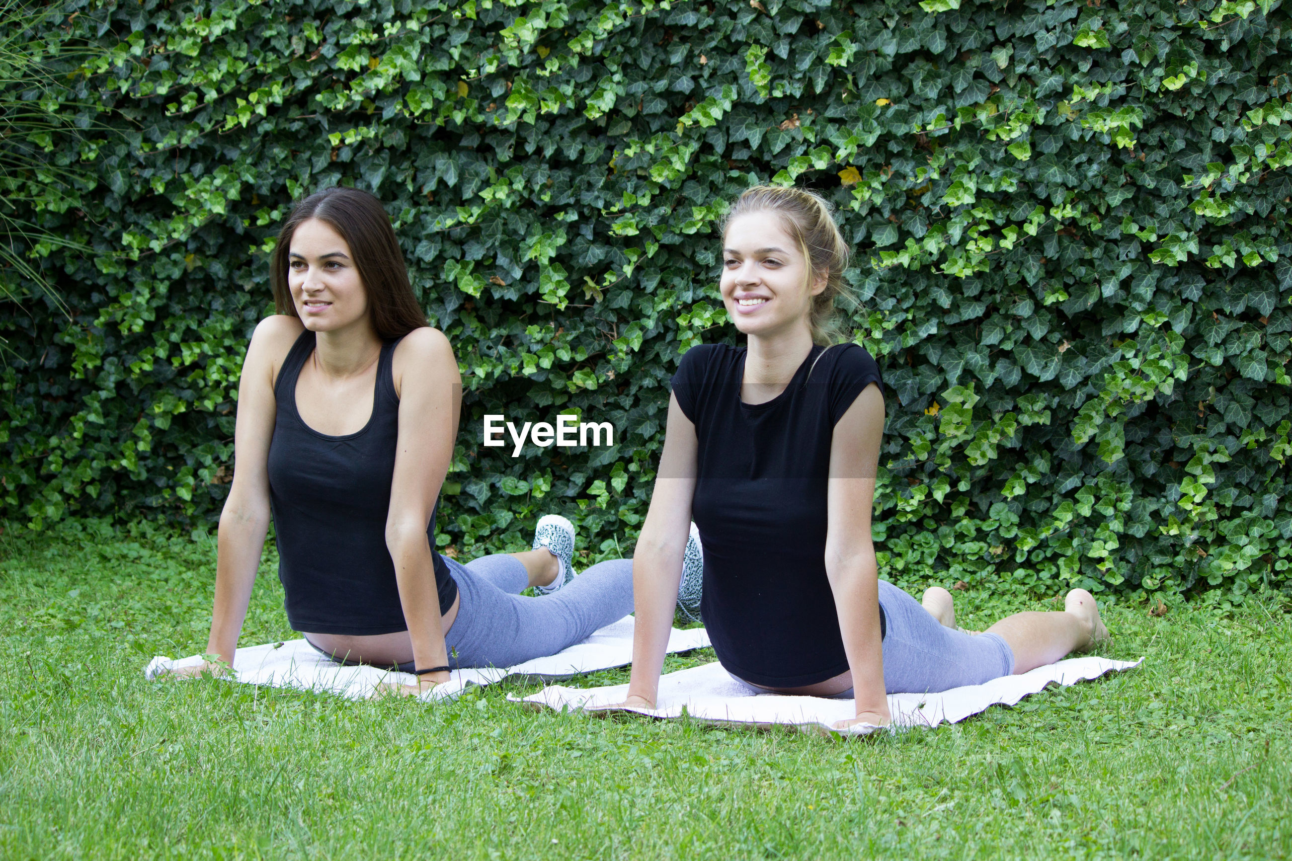 Smiling friends looking away while exercising against plants in park
