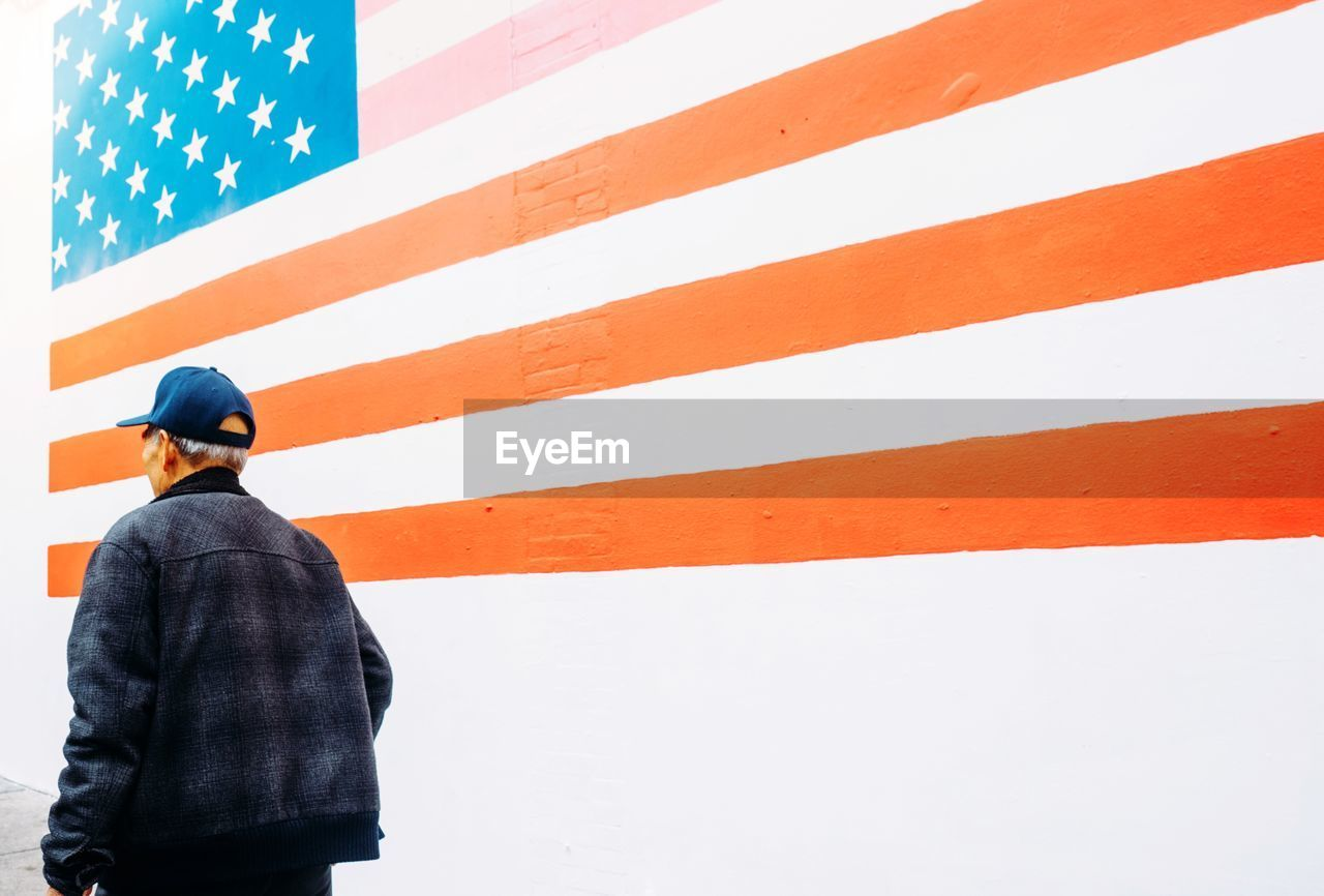 Rear view of man walking by american flag painted on wall