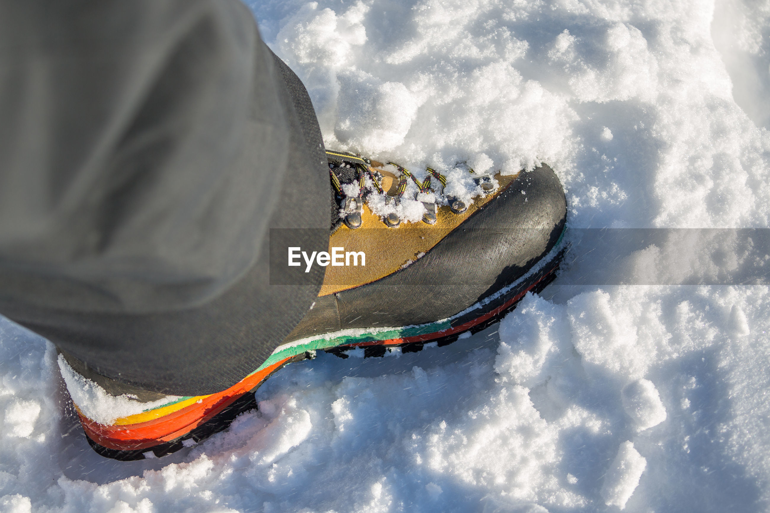 Low section of person wearing hiking boots on snow