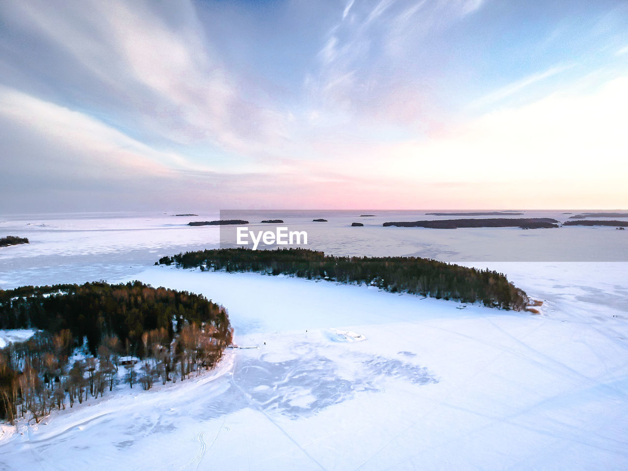 SCENIC VIEW OF FROZEN LAKE DURING SUNSET
