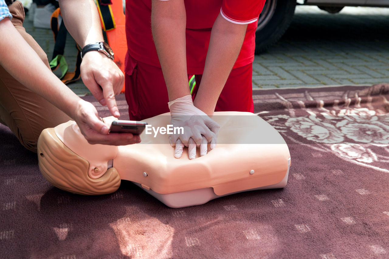 Midsection Of Man Showing Phone To Woman Practicing On Cpr Dummy