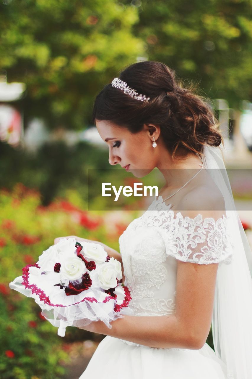 Side View Of Bride Holding Flower Bouquet