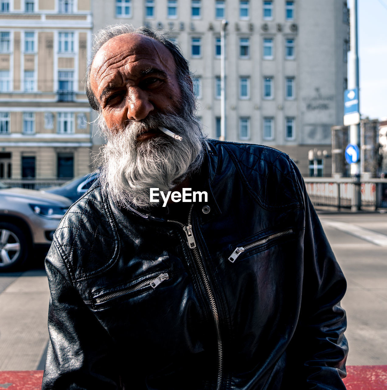 senior adult, city, one person, facial hair, beard, real people, architecture, lifestyles, portrait, males, men, adult, senior men, looking at camera, waist up, day, city life, focus on foreground, jacket, white hair, outdoors, hairstyle