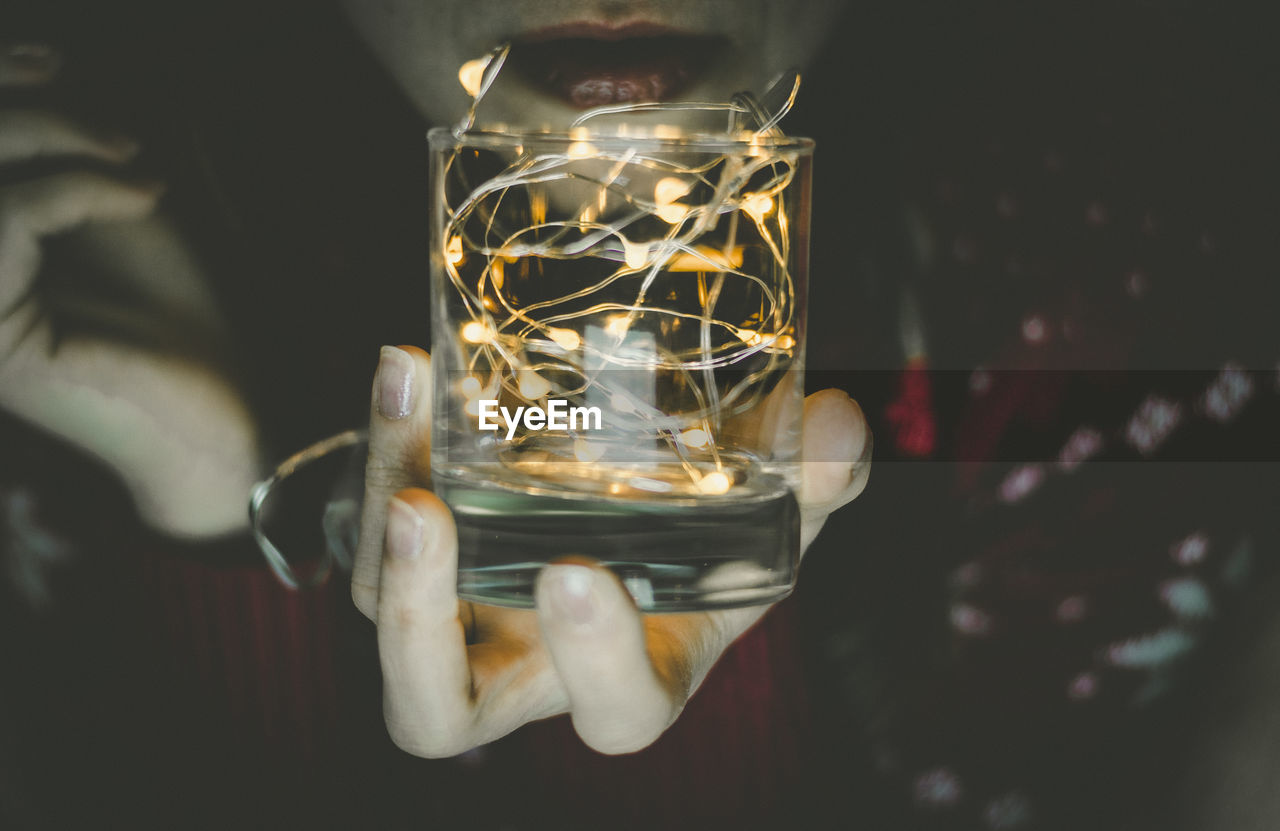 Midsection Of Woman Holding Glass With Illuminated String Light
