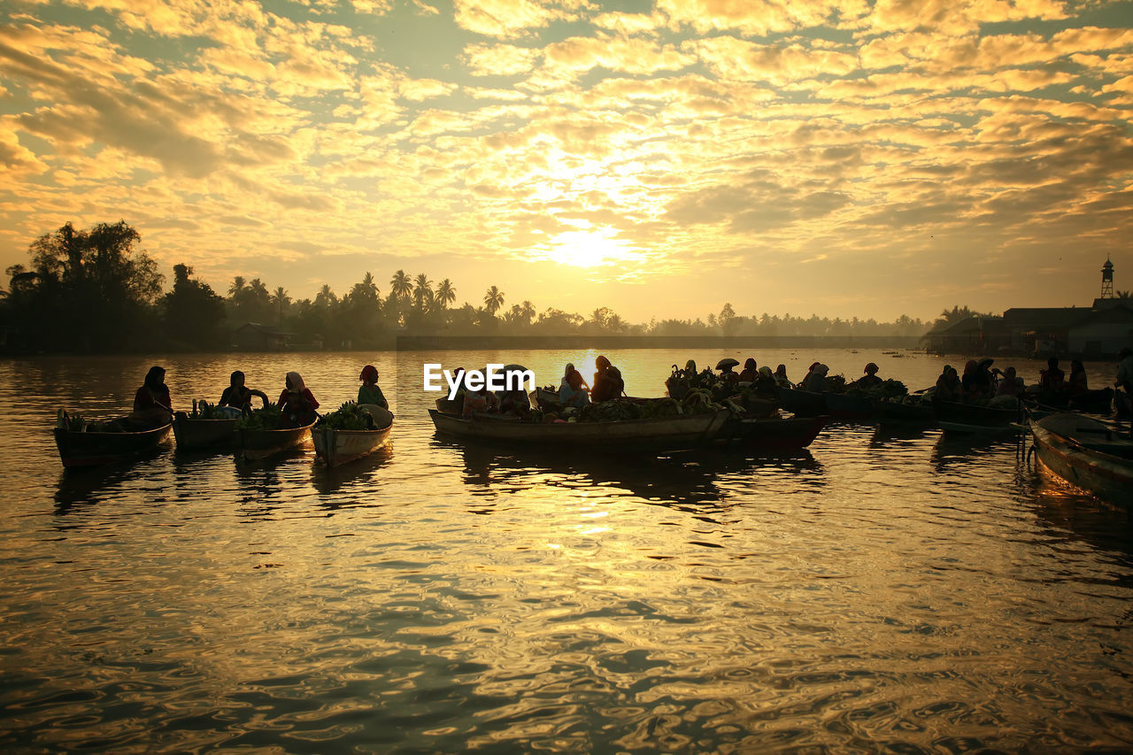 Silhouette People On Boats In Lake Against Sky During Sunset