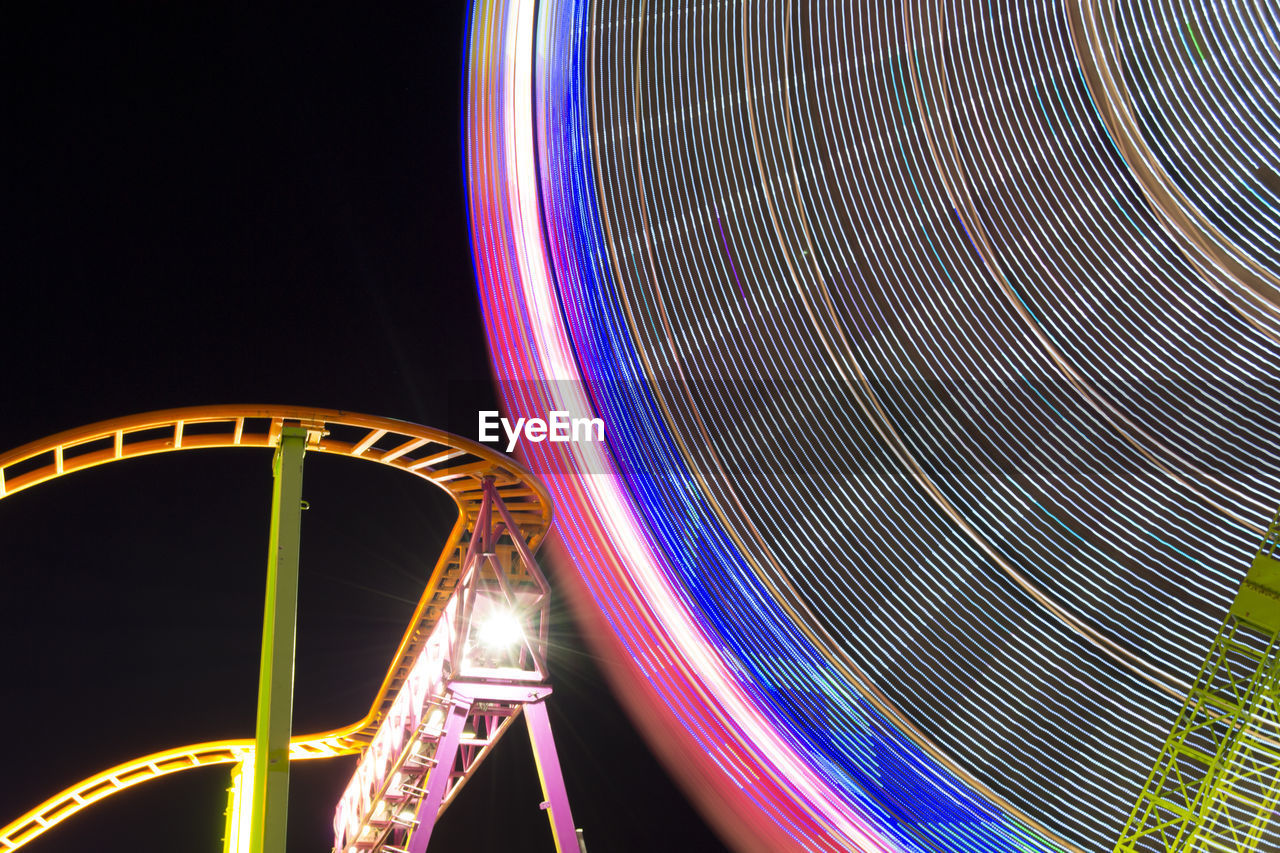 amusement park, arts culture and entertainment, night, amusement park ride, motion, illuminated, long exposure, light trail, speed, low angle view, blurred motion, outdoors, ferris wheel, leisure activity, multi colored, no people, excitement, carousel, sky