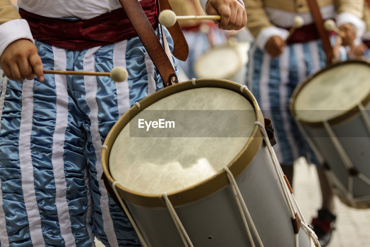 Midsection of men playing drums