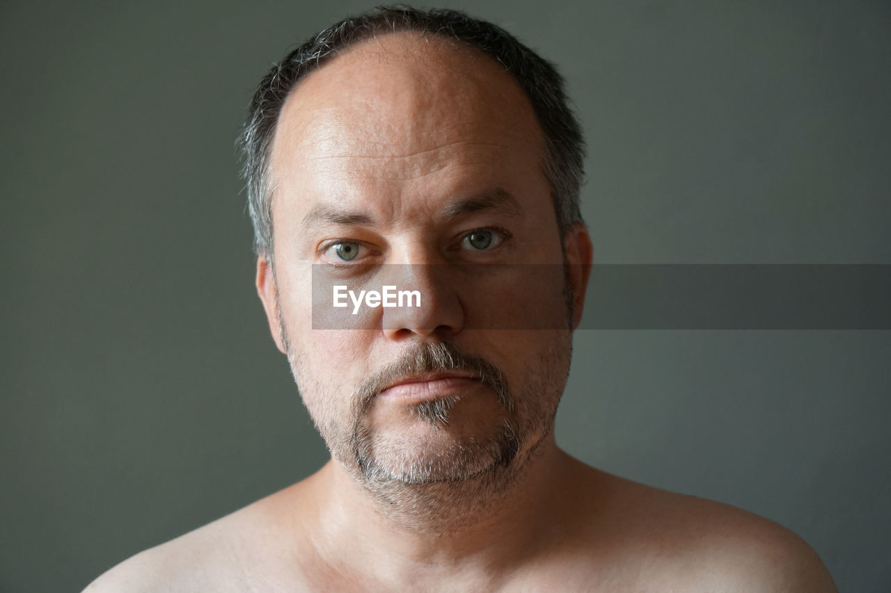 Portrait of shirtless man against gray background