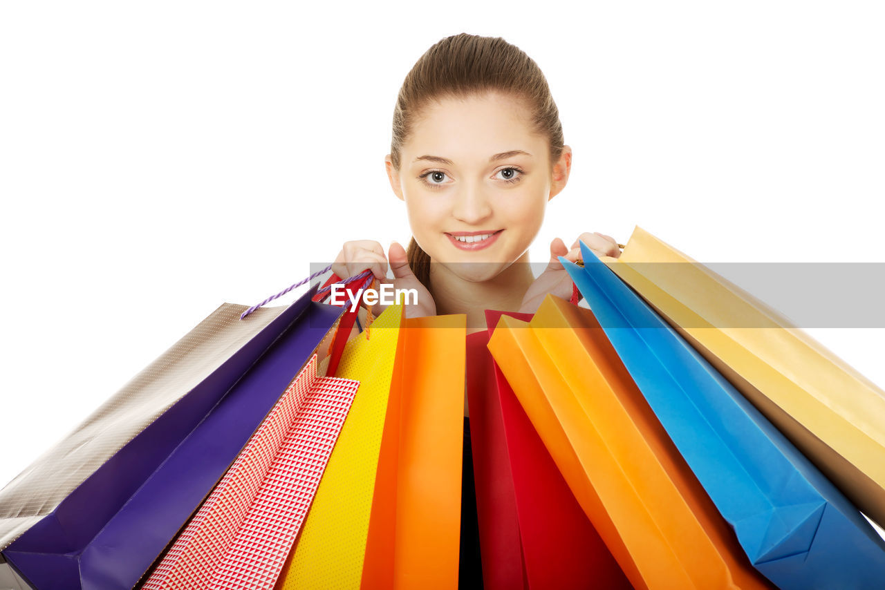 Portrait Of Young Woman Holding Shopping Bags Against White Background