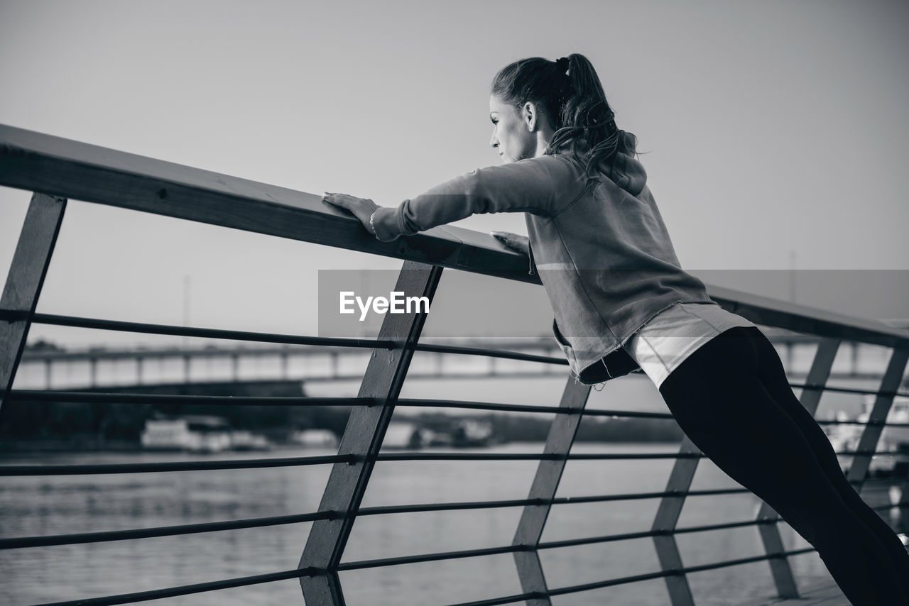 one person, railing, lifestyles, real people, architecture, full length, side view, focus on foreground, sky, day, built structure, outdoors, leisure activity, sport, young adult, nature, looking, clear sky, hairstyle, effort