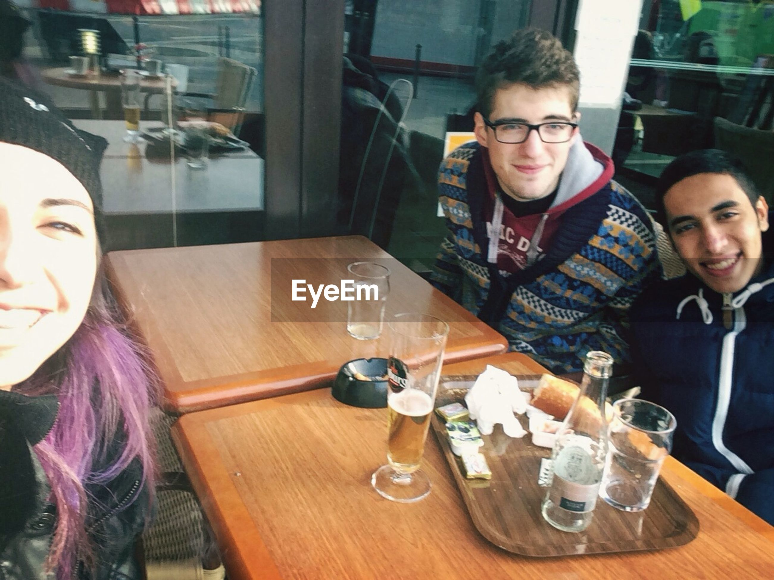 indoors, person, lifestyles, young adult, leisure activity, table, casual clothing, drink, young women, restaurant, food and drink, sitting, smiling, front view, portrait, looking at camera, glass - material
