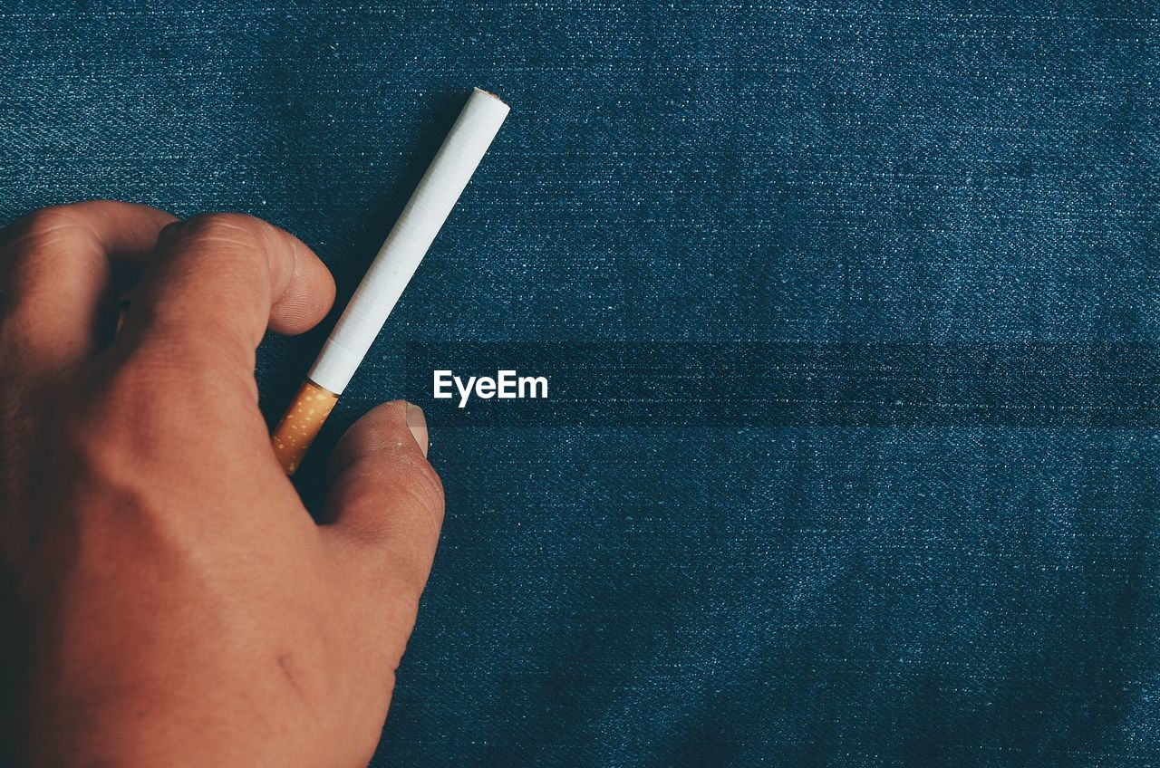 Close-Up Of Human Hand Picking Up Cigarette