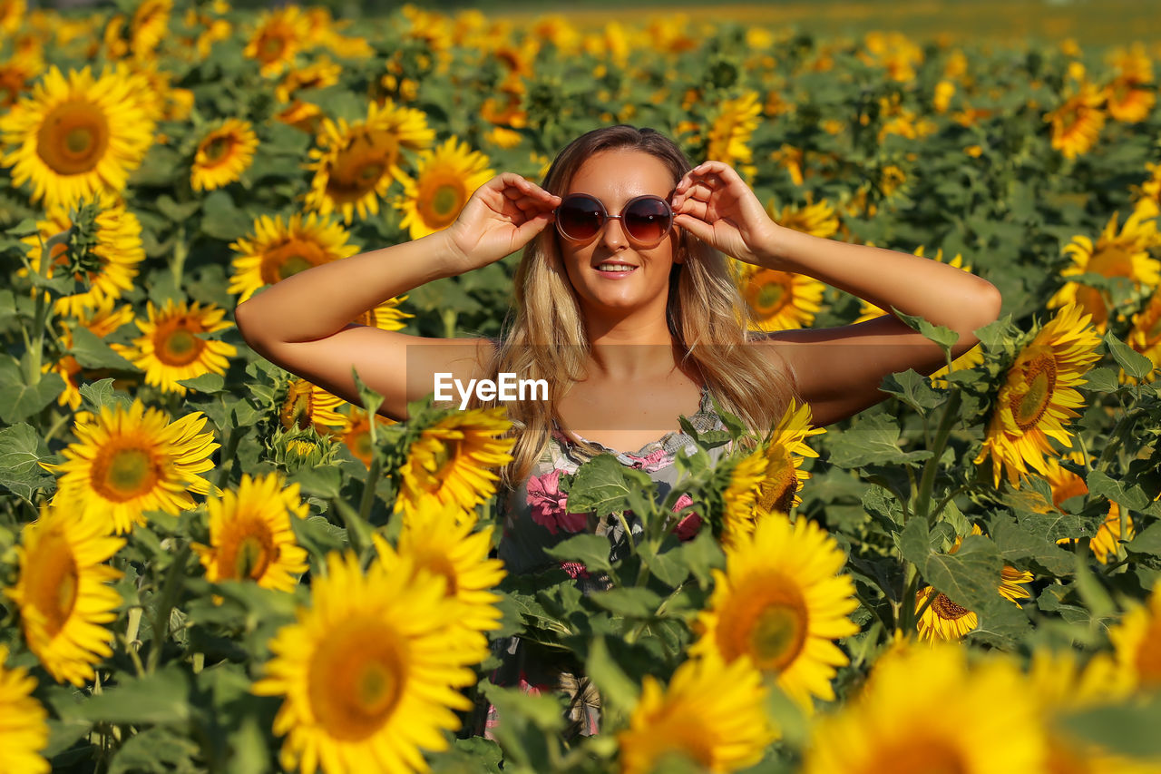 one person, flowering plant, flower, smiling, plant, leisure activity, lifestyles, portrait, real people, happiness, yellow, sunglasses, front view, young adult, glasses, fashion, beauty in nature, looking at camera, nature, freshness, outdoors, flower head, human arm, beautiful woman