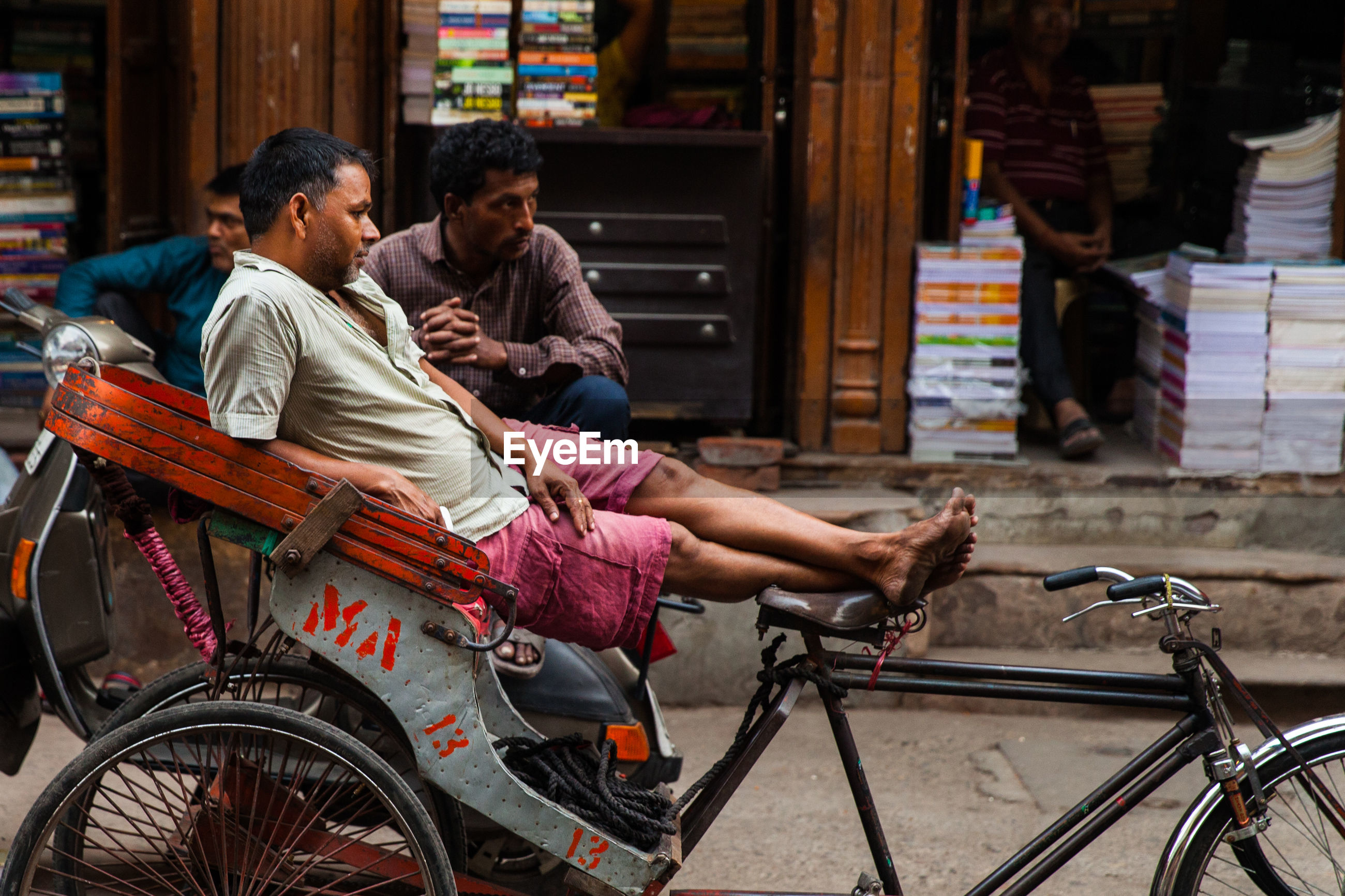 PEOPLE SITTING ON BICYCLE AT A AN ABANDONED