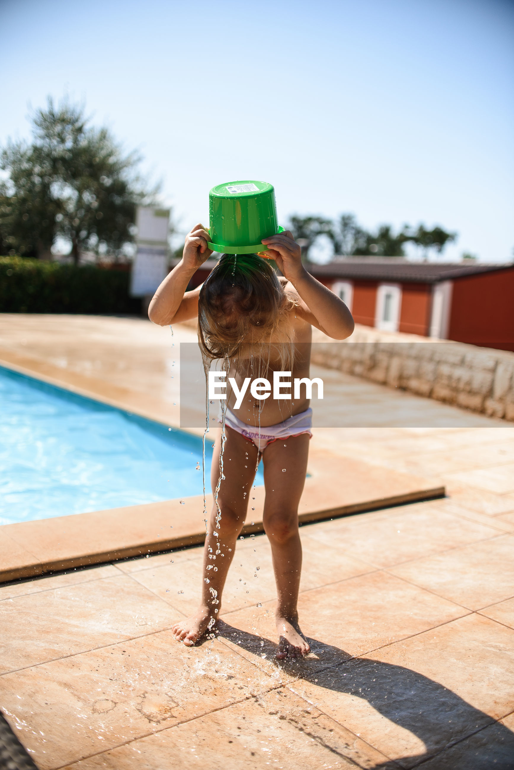 FULL LENGTH REAR VIEW OF GIRL STANDING AT SWIMMING POOL