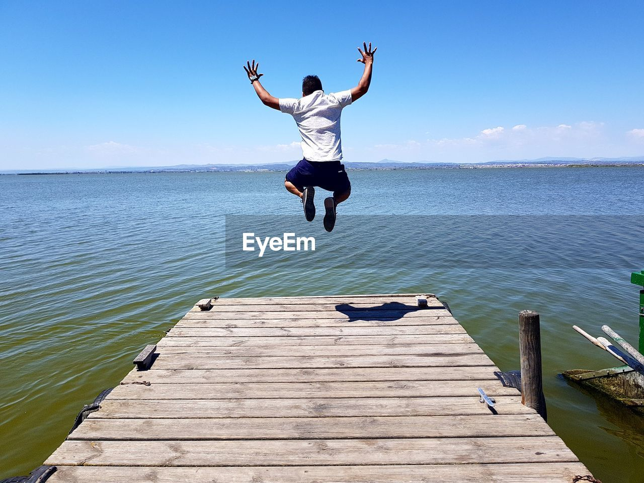 Rear View Of Man Jumping On Pier Over Sea Against Sky