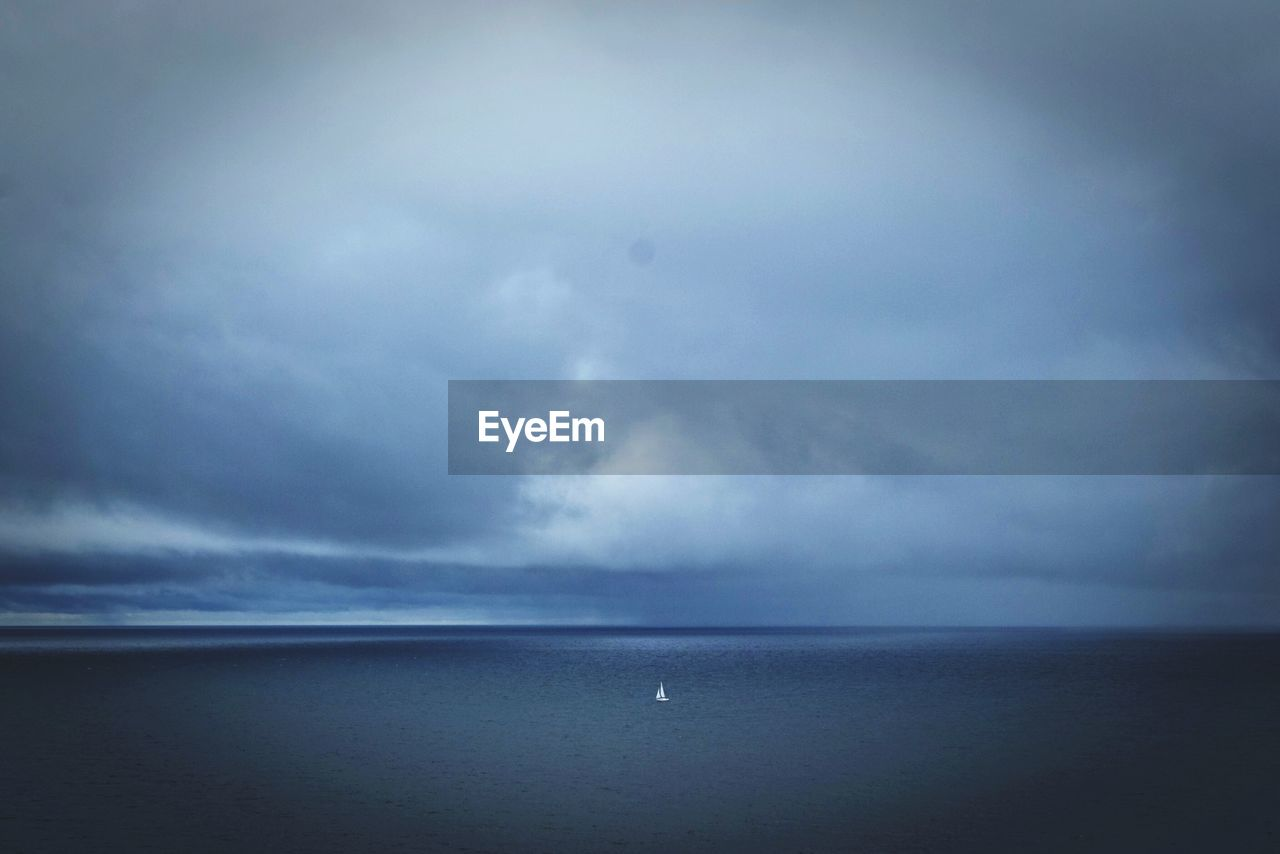 Scenic view of sea against cloudy sky at dusk