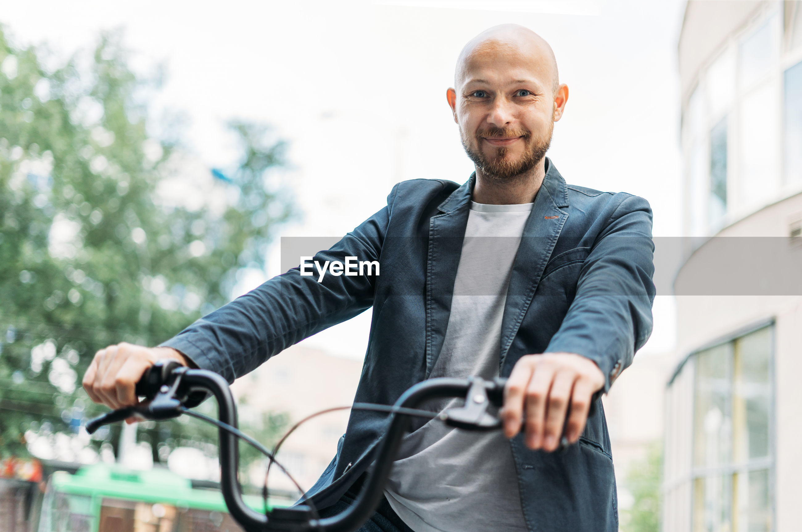 Portrait of man holding bicycle standing outdoors