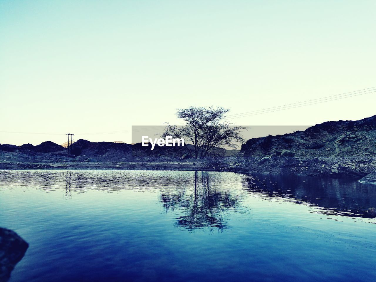water, sky, clear sky, tranquility, nature, copy space, tranquil scene, reflection, beauty in nature, scenics - nature, no people, waterfront, lake, tree, mountain, blue, day, outdoors, environment