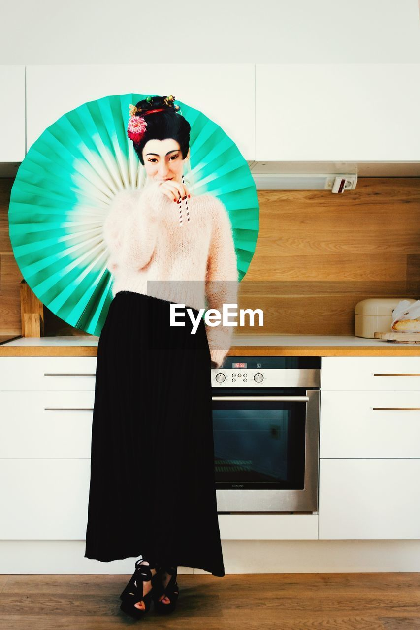 Woman Dressed As Geisha Standing In Kitchen