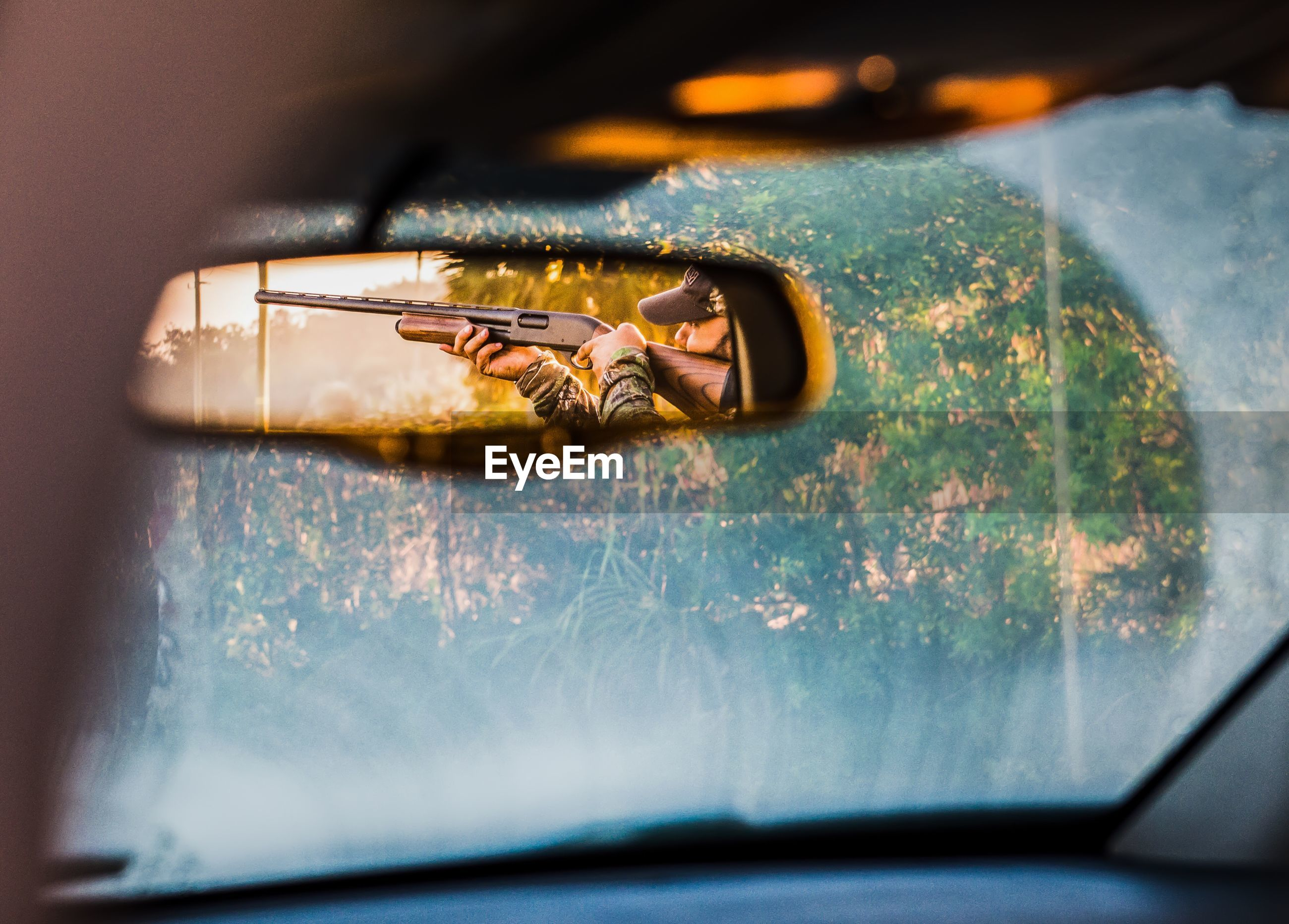 Hunter aiming with shotgun reflecting in rear-view mirror of car
