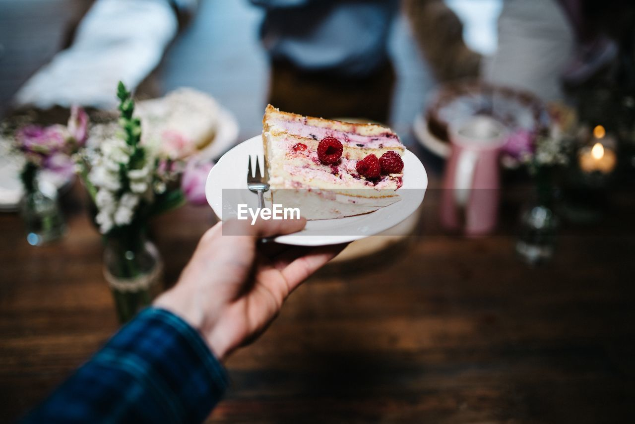 Close-Up Of Cropped Hand Holding Cake Slice In Plate