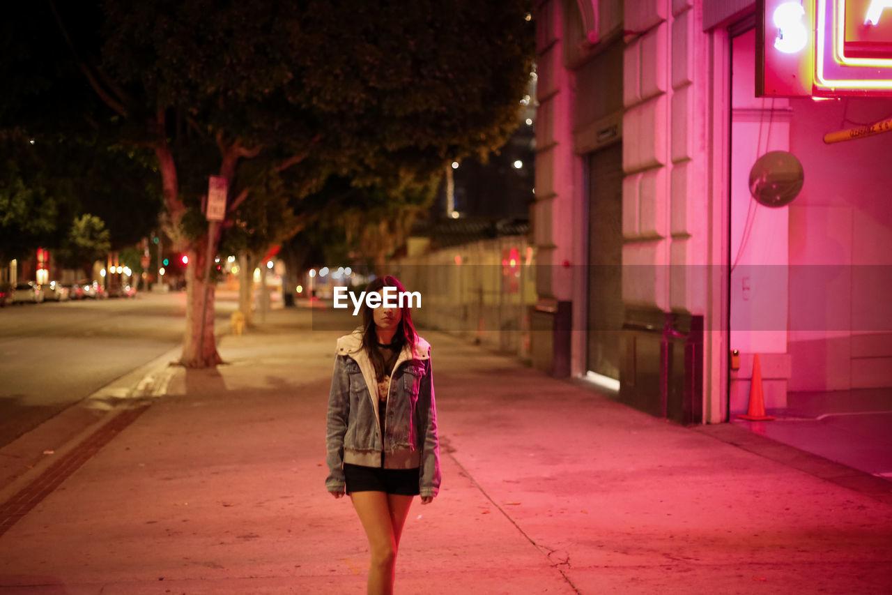 Woman walking on sidewalk at night