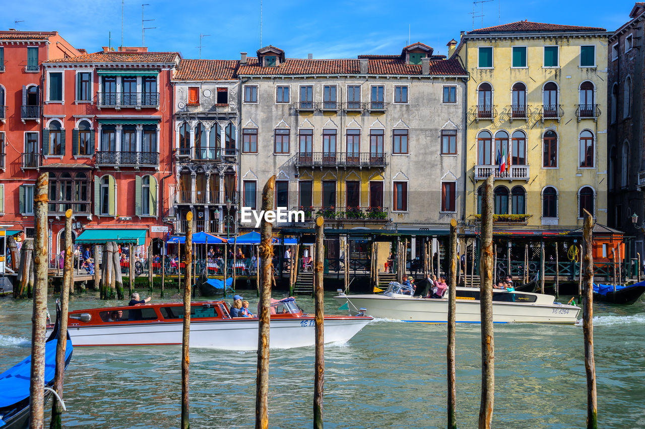 building exterior, water, built structure, architecture, building, waterfront, nature, nautical vessel, city, day, transportation, canal, mode of transportation, travel destinations, sky, residential district, wooden post, group of people, large group of people, outdoors, post