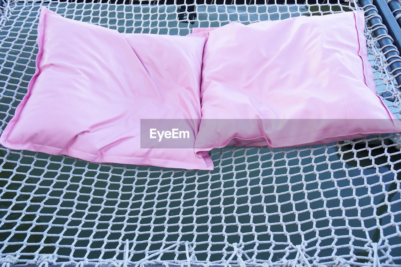 HIGH ANGLE VIEW OF PINK FABRIC ON BED