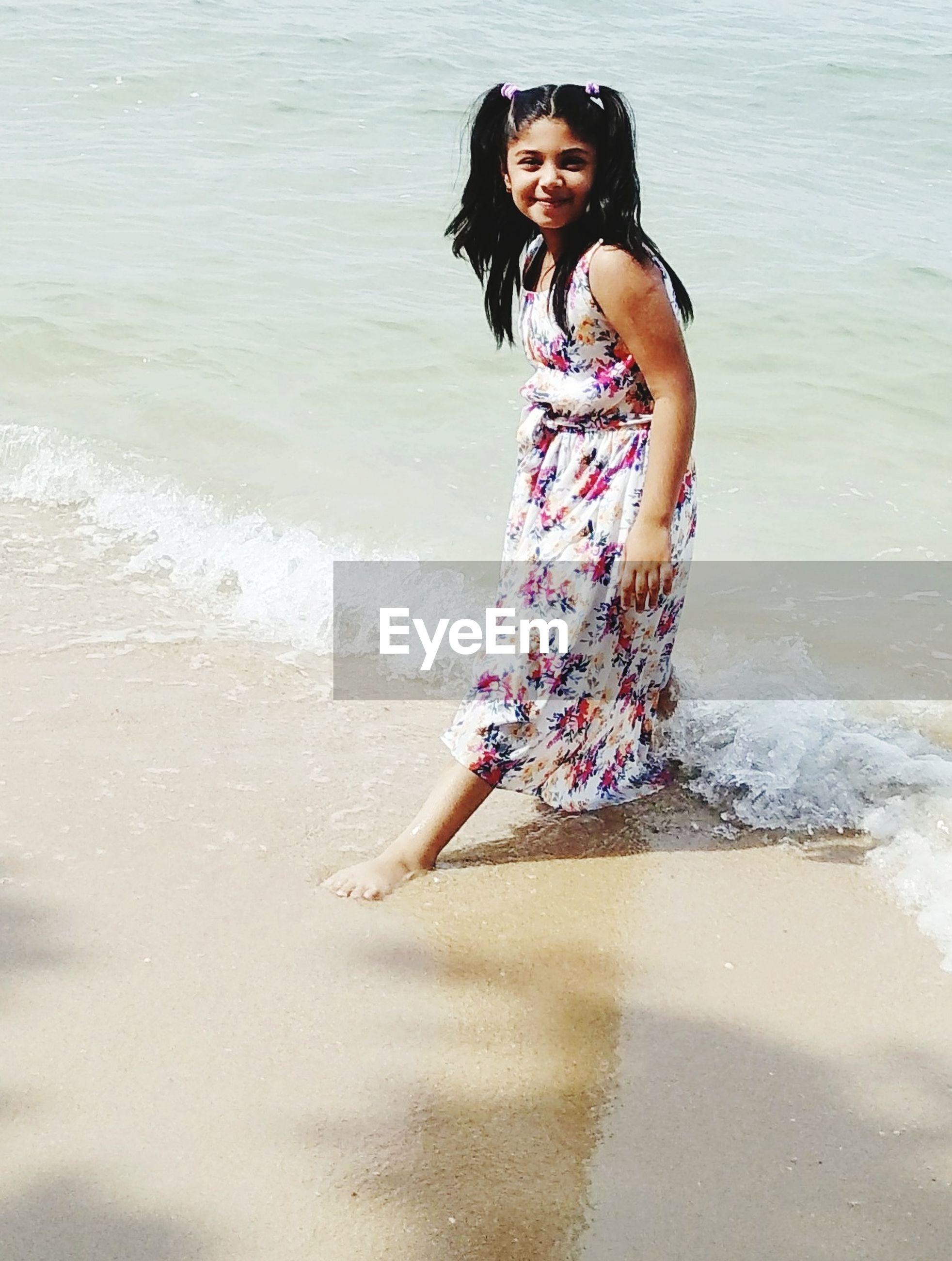 Portrait of cute girl standing in sea