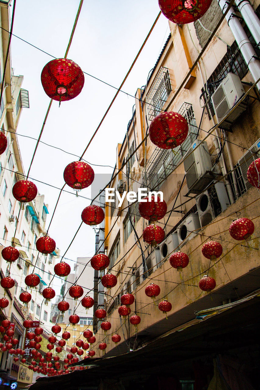 low angle view, hanging, lantern, red, no people, decoration, lighting equipment, building exterior, architecture, built structure, chinese lantern, celebration, holiday, building, day, nature, large group of objects, chinese new year, festival