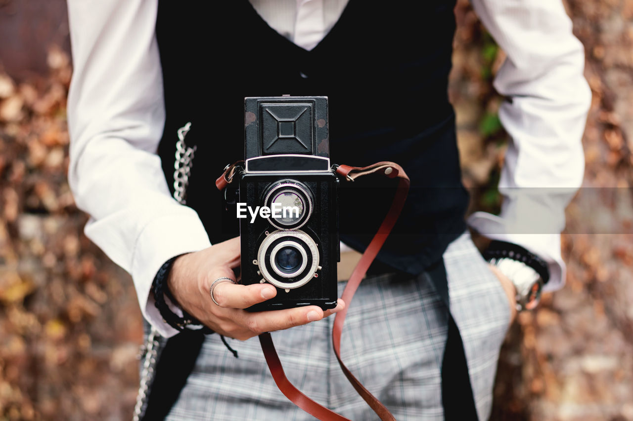 Close-up of man photographing with vintage medium format photo camera outdoors.